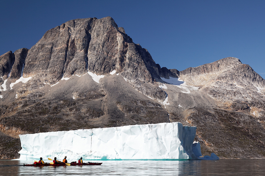 Sea kayakers paddling on Ikaasatsivaq Fjord below mountain and tabular iceberg, Ammassalik Island, East Greenland