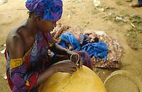 Woman repairing  calebash