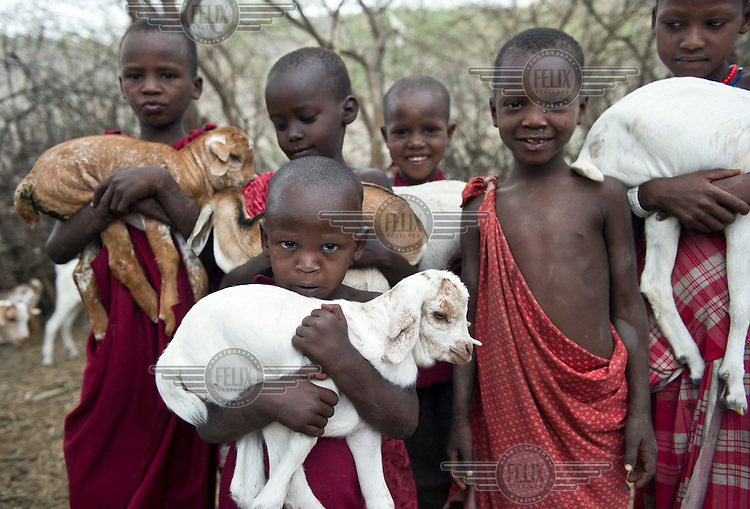 Masaai children holding small goats in a kraal, an enclosure for cattle or other livestock, on the road between Arusha and Loliondo. The government of Tanzania is planning to turn this dirt track into a highway that will connect isolated communities and bring much needed development to the marginalised Masaai. However, the highway will cut straight through the Serengeti National Park, a World Heritage Site, disrupting animal migration, which would have disastrous consequences for the entire park ecosystem.
