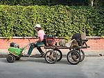 Small tiller-powered cart with saw driving a street in Kazanlak, Bulgaria