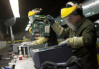 12/4/2008 3:31:21 PM -- Seattle, WA.Nelson Andrade, 27, of of Seattle pulls out the motherboard while breaking down a computer Total Reclaim Inc., Environmental Services in Seattle Thursday Dec. 4, 2008.