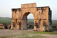 The Triumphal Arch of Caracalla, built 217 AD by the city's governor Marcus Aurelius Sebastenus in honour of Emperor Caracalla, 188-217 AD, and his mother Julia Domna, Volubilis, Northern Morocco. The arch was reconstructed 1930-34 and was originally topped with a bronze chariot pulled by 6 horses. The medallion busts are portraits of Caracalla and Julia Domna. Volubilis was founded in the 3rd century BC by the Phoenicians and was a Roman settlement from the 1st century AD. Volubilis was a thriving Roman olive growing town until 280 AD and was settled until the 11th century. The buildings were largely destroyed by an earthquake in the 18th century and have since been excavated and partly restored. Volubilis was listed as a UNESCO World Heritage Site in 1997. Picture by Manuel Cohen