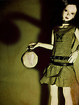 portrait of a doll holding a little round bag