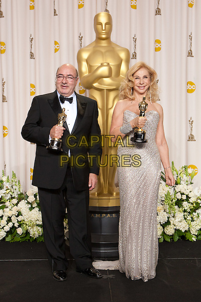 """Art direction Oscar® goes to, Dante Ferretti for production design and Francesca Lo Schiavo for set decoration, winner for Achievement in Art Direction for work on """"Hugo"""", pose backstage for the media during the 84th Annual Academy Awards® broadcast by the ABC Television Network from the Hollywood and Highland Center, in Hollywood, CA, Sunday, February 26, 2012..*Editorial Use Only*.oscars award trophy winner full length black tuxedo silver dress.CAP/A.M.P.A.S./NFS.©A.M.P.A.S. Supplied by Capital Pictures."""