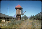 Jacks Cabin water tank. Child at base of tank. Crested Butte Mt. to left of tank in background.<br /> D&amp;RGW  Jacks Cabin, CO