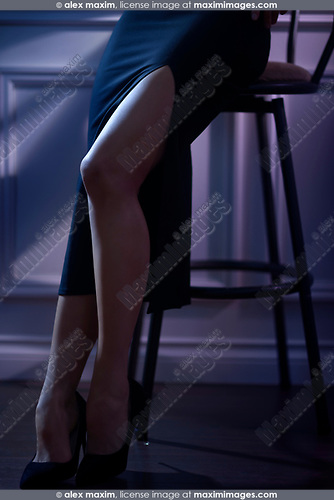 Closeup of sexy legs of a woman wearing a tight black skirt with a long high cut sitting on a bar stool in a dimly lit room