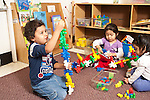 Education preschool 2-3 year olds three children playing separately boy and girl with colorful plastic connecting pieces and girl with colorful plastic sorting bears