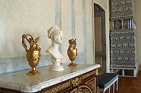 An alabaster bust is flanked by a pair of gold jugs on a marble-topped sideboard in this marble panelled room