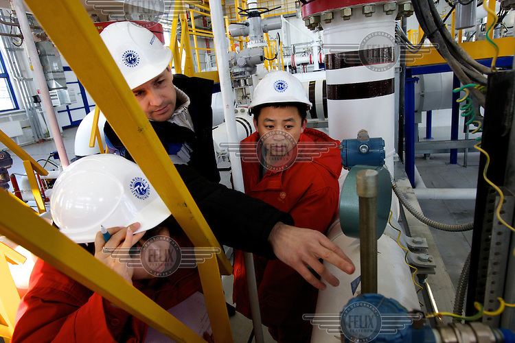 Jia Yanping (left), 24, a Chinese engineer monitors oil quality at the Russian pump station in Dzhalinda, run by Russian oil company Transneft, supplying oil to energy-hungry China across the border. Standing next to her is Yuri Kolesnikov, 33, chief of the station, and Chinese engineer Zao Dawei, 34.