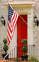 An American Flag hangs outside of a home in the Myers Park neighborhood in Charlotte, NC. Myers Park is one of the premier neighborhoods in North America and known for its large canopy of trees.