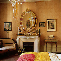 A traditional yellow bedroom. A gilt oval mirror hangs above a carved marble fireplace.