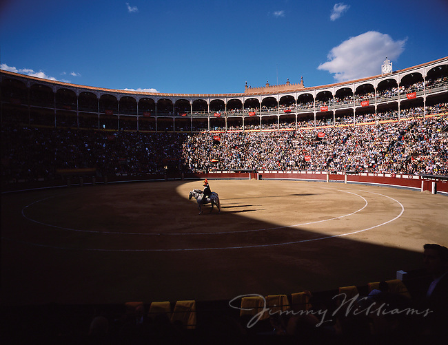 Men on horses sit in the center of a bull fighting stadium in Madrid, Spain