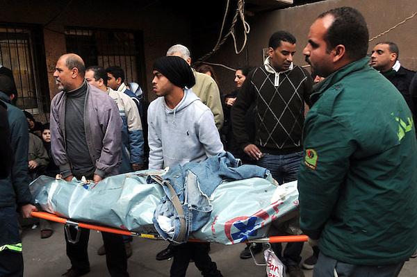 """EGY01 EL CAIRO (EGIPTO) 02/02/2012.- Egipcios trasladan el cadáver de una de las 74 víctimas de la tragedia ocurrida anoche en un estadio de fútbol en Port Said hasta un tanatorio en El Cairo (Egipto), hoy, jueves 2 de febrero de 2012. El primer ministro egipcio, Kamal Ganzuri, reconoció hoy su responsabilidad política por los disturbios de anoche en un partido de fútbol en Port Said y dijo que está dispuesto a rendir cuentas si se lo piden. """"Estoy dispuesto a cumplir con cualquier instrucción que me pida rendir cuentas, porque sé que soy responsable políticamente"""", dijo Ganzuri en un discurso ante el Parlamento, que hoy celebra una reunión de urgencia para analizar los sucesos. EFE/Str"""