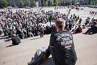"""10. Berliner Karfreitagsprozession am Freitag den 19. April 2019.<br /> Mehrere hundert Menschen zogen hinter einem grossen Holzkreuz von der St. Marienkirche durch die Innenstadt zum Gendarmenmarkt. Die Prozession erinnerte an den Fall der Berliner Mauer vor 30 Jahren und Mauern und Grenzen weltweit, an denen Menschen nach wie vor leiden muessen.<br /> Initiiert wurde die Prozession vom Evangelischen Kirchenkreis Berlin Stadtmitte.<br /> Im Bild: Ein Tourist mit einem """"Buddah""""-T-Shirt betrachtet den Abschluss der Prozession auf dem Gendarmenmarkt.<br /> 19.4.2019, Berlin<br /> Copyright: Christian-Ditsch.de<br /> [Inhaltsveraendernde Manipulation des Fotos nur nach ausdruecklicher Genehmigung des Fotografen. Vereinbarungen ueber Abtretung von Persoenlichkeitsrechten/Model Release der abgebildeten Person/Personen liegen nicht vor. NO MODEL RELEASE! Nur fuer Redaktionelle Zwecke. Don't publish without copyright Christian-Ditsch.de, Veroeffentlichung nur mit Fotografennennung, sowie gegen Honorar, MwSt. und Beleg. Konto: I N G - D i B a, IBAN DE58500105175400192269, BIC INGDDEFFXXX, Kontakt: post@christian-ditsch.de<br /> Bei der Bearbeitung der Dateiinformationen darf die Urheberkennzeichnung in den EXIF- und  IPTC-Daten nicht entfernt werden, diese sind in digitalen Medien nach §95c UrhG rechtlich geschuetzt. Der Urhebervermerk wird gemaess §13 UrhG verlangt.]"""