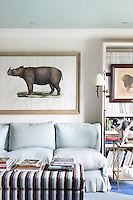 One wall of the living room is dominated by a pale blue linen sofa beneath a framed illustration of a rhino