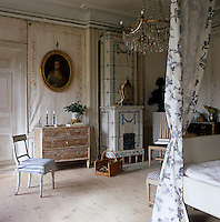 The large master bedroom has walls covered in linen canvas panels and a neoclassical tiled stove