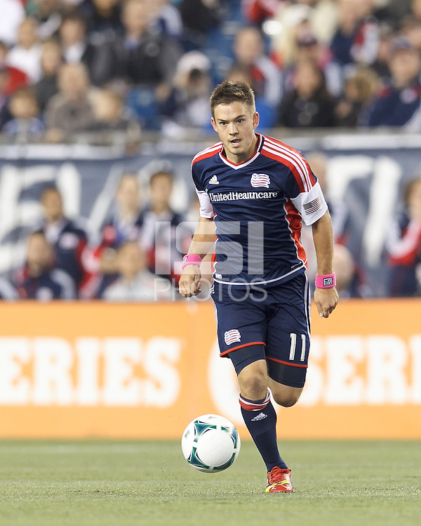 New England Revolution midfielder Kelyn Rowe (11) brings the ball forward.  In a Major League Soccer (MLS) match, the New England Revolution (blue) defeated Columbus Crew (white), 3-2, at Gillette Stadium on October 19, 2013.