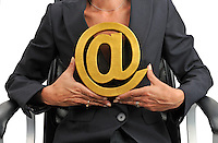 Businesswoman holding At Symbol in hands (Licence this image exclusively with Getty: http://www.gettyimages.com/detail/106421918 )