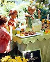 A boy serving lemonade to his friends at an outdoor party