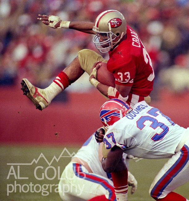 San Francisco 49ers vs Buffalo Bills at Candlestick Park Sunday, December 17, 1989..49ers beat Bills 21-10.San Francisco 49er running back Roger Craig (33) high steps over Bills defensive back Nate Odomes (37) ..