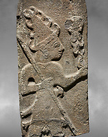 Close up of Hittite monumental relief sculpture ofa God probably holding lightning rods. Late Hittite Period - 900-700 BC. Adana Archaeology Museum, Turkey. Against a grey art background