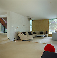 A large curved sofa dominates the open-plan home cinema and an oatmeal coloured rug covers the polished limestone floor