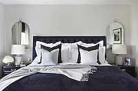 The emperor bed in the master bedroom, furnished in deep, subtly patterned blues and soft whites