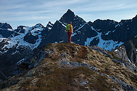 Female hiker on summit of Flakstadtind mountain peak, Flakstadøy, Lofoten Islands, Norway