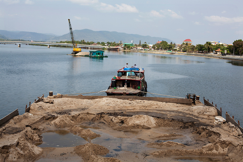 A partially full sand barge passes under a bridge on the Kampong bay river, Kampot province, Cambodia, February 10, 2012.