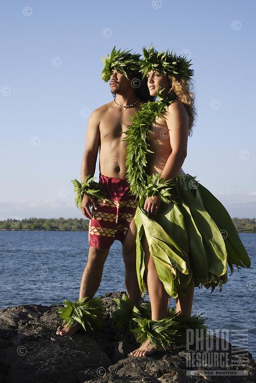 Kane (male) and wahine (female) hula dancers wearing palapalai fern head lei look out to sea.