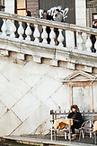 ITALY, Venice. A young woman drinking an espresso at a cafe at the Rialto Bridge.