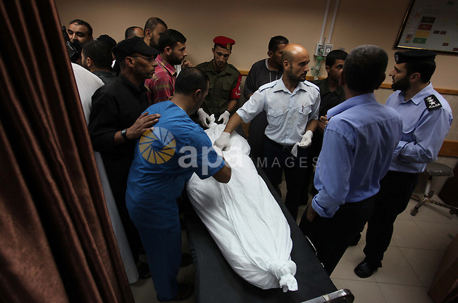 Hospital workers handle the of a man that was killed when the Al-Qassam mosque was targeted by an Israeli airstrike in the early morning hours in Nuseirat in Gaza City on August 9, 2014. Israeli warplanes carried out 30 air strikes over Gaza, killing five Palestinians, as militants fired six rockets into Israel, leaving international mediators scrambling to rescue ceasefire talks. Photo by Ramadan El-Agha