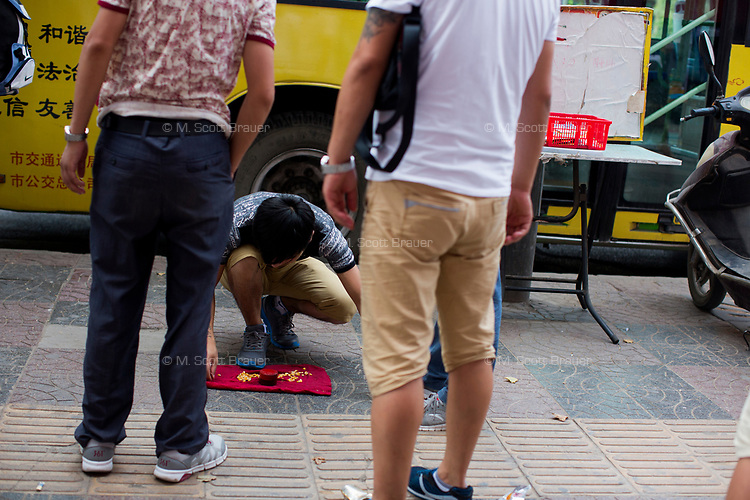 A man runs a gambling game on the sidewalk in Xian, Shaanxi, China.