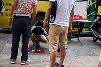 A man runs a gambling game on the sidewalk in Xian, Shaanxi, China.