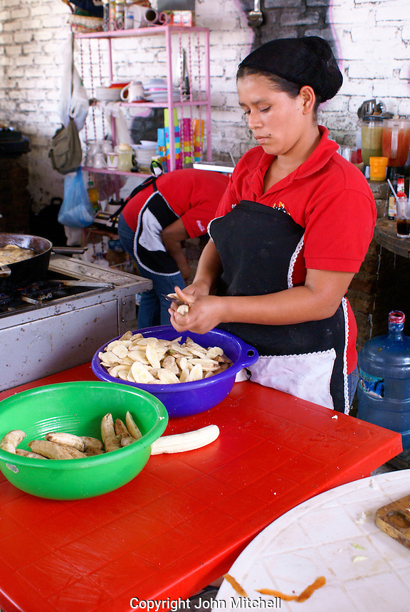 Young Honduran woman slicing plantains in a restaurant, Santa Rosa de Copan, Honduras.