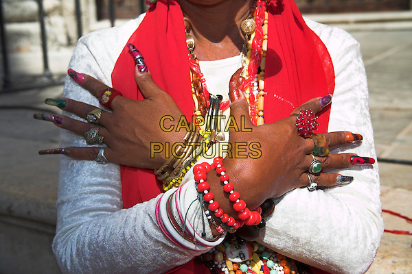 Lady wearing colourful jewellery, arms crossed, decorated finger nails, Plaza de la Catedral, Havana, La Habana Vieja, Cuba