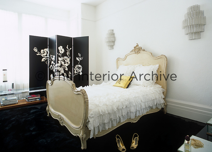 This black and white bedroom is dominated by a French-style bed and a contemporary screen