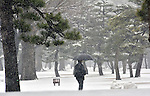 February 14, 2014, Tokyo, Japan - A lone walker slogs through the pile of snow on the Imperial Palace outer garden in Tokyo on Friday, February 14, 2014. Two weeks in a row, the nation's capital was blanketed with inches of snow as a low-pressure front hit a wide swath along the Pacific coasts, disrupting land, sea and air transportation services.  (Photo by Natsuki Sakai/AFLO)