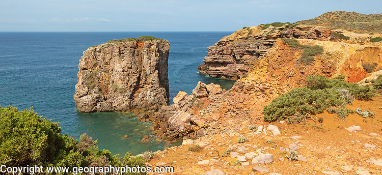 Coastal stacks and orange coloured crumbling  cliffs rise from Atlantic Ocean at Cabo de São Vicente, Cape St Vincent, Algarve, Portugal, southern Europe