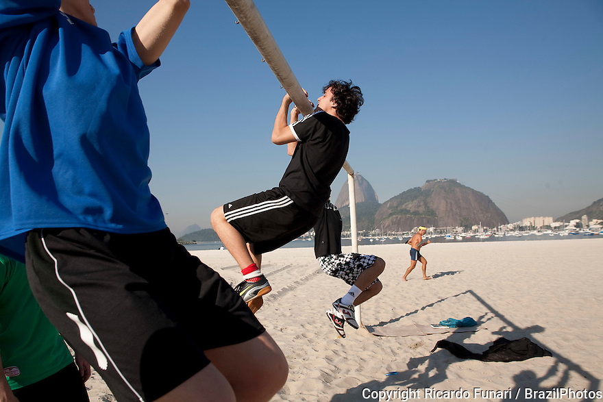 Young men exercise at goal post in Botafogo beach in Rio de Janeiro, Brazil - Sugar Loaf mountain in background.