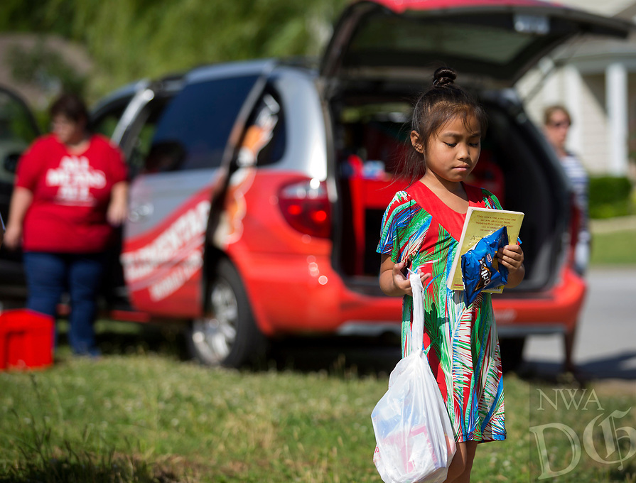 NWA Democrat-Gazette/JASON IVESTER<br /> Alyssa John, a rising second-grader, looks over her book selection and snacks Tuesday, June 13, 2017, from the Sonora Elementary Mobile Library during its stop at the playground on Commons Avenue in Springdale.
