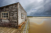 The old unused wooden wharf building on the Okarito lagoon, Westland District, West Coast, South Island, New Zealand.