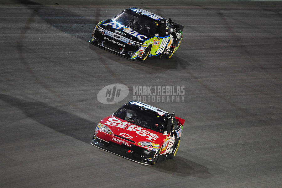 Nov. 20, 2011; Homestead, FL, USA; NASCAR Sprint Cup Series driver Tony Stewart (14) leads Carl Edwards (99) during the Ford 400 at Homestead Miami Speedway. Mandatory Credit: Mark J. Rebilas-