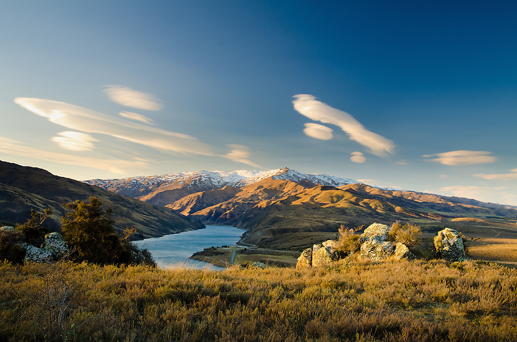 View of lenticular clouds, Leaning Rock and Lake Dunstan from the Clyde Lookout at sunset, Central Otago, New Zealand - stock photo, canvas, fine art print