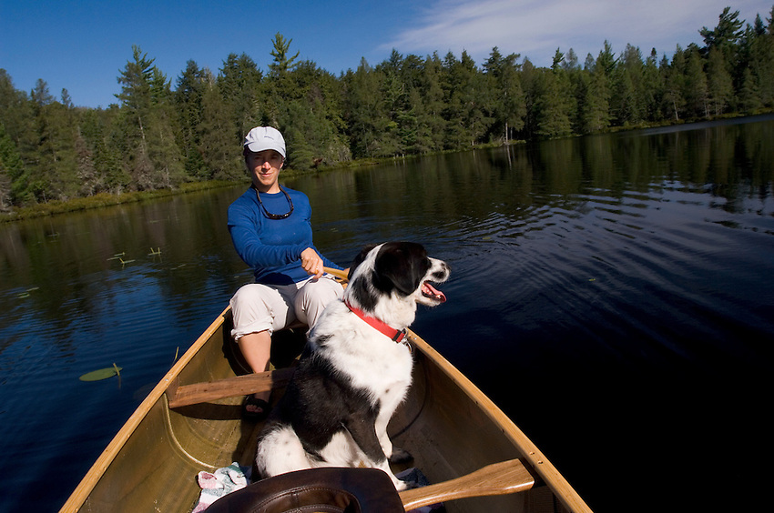 A female canoeist and her dog in the stern of a canoe at Florence Lake at Sylvania Wilderness Area of Ottawa National Forest near Watersmeet Michigan.