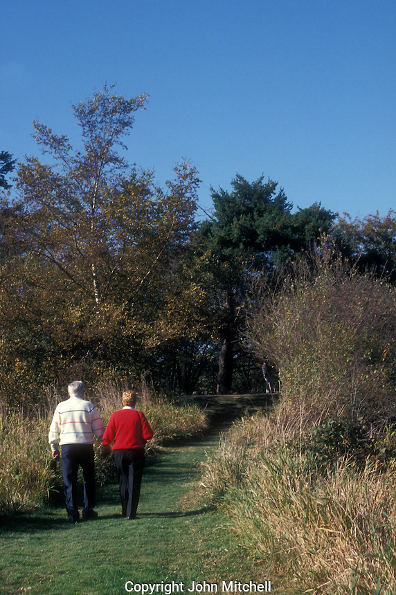 Older couple walking hand in hand along a trail at the George C. Reifel Migratory Bird Sanctuary in Delta, BC, Canada.