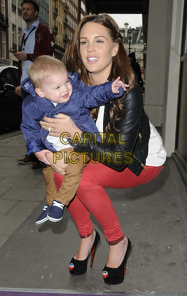 Danielle Lloyd & her son.The launch of the Disney TV Series 'Sofia The First' at the Mayfair Hotel, London, England..22nd February 2013.full length black leather jacket white shirt leopard print trim red jeans denim black platform peep toe shoes kid child mother mom mum kid child crouching carrying holding blue.CAP/CAN.©Can Nguyen/Capital Pictures.