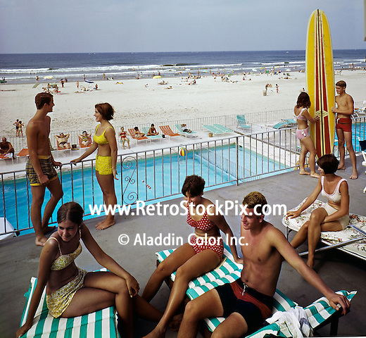Group of teens relaxing on the sundeck of the Commander Motel in Wildwood, New Jersey. Bikinis and long surfboards. 1960's retro photograph.