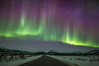Colorful northern lights over the James Dalton Highway and the Brooks Range mountains in Alaska's Arctic.