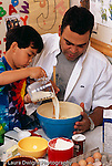 4 year old boy with father cooking and baking in kitchen vertical pouring milk from measuring cup